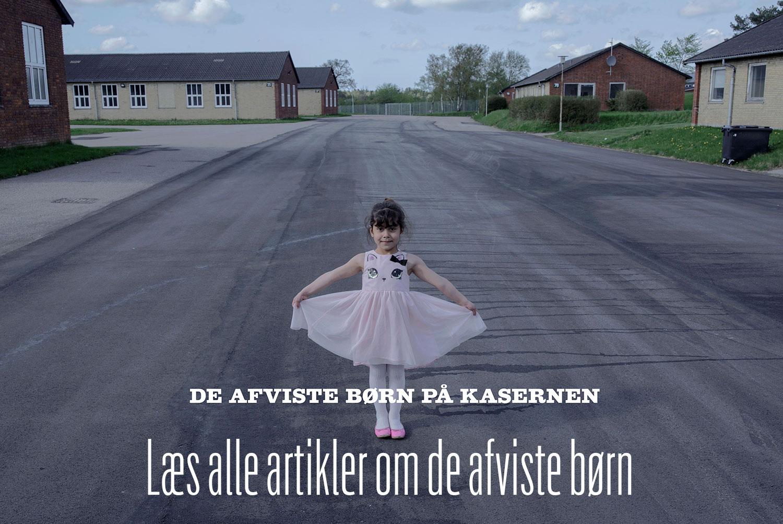 Pige står med spredte arme i indkørslen til Sjælsmark asylcenter